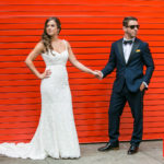 bride and groom posing red door